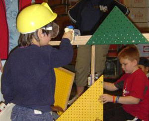 Kids in hard hats building at the Dunn Lumber construction center in the Children's Museum